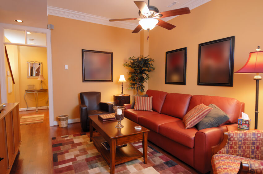 A Small Family Room Tucked Into A Nook That Includes A Bold Red Faux Leather Couch