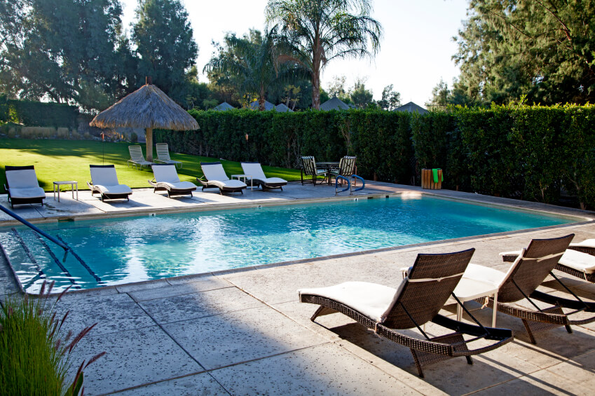 this pool and patio offers comfort and privacy with a neatly trimmed hedge wall bracketing the