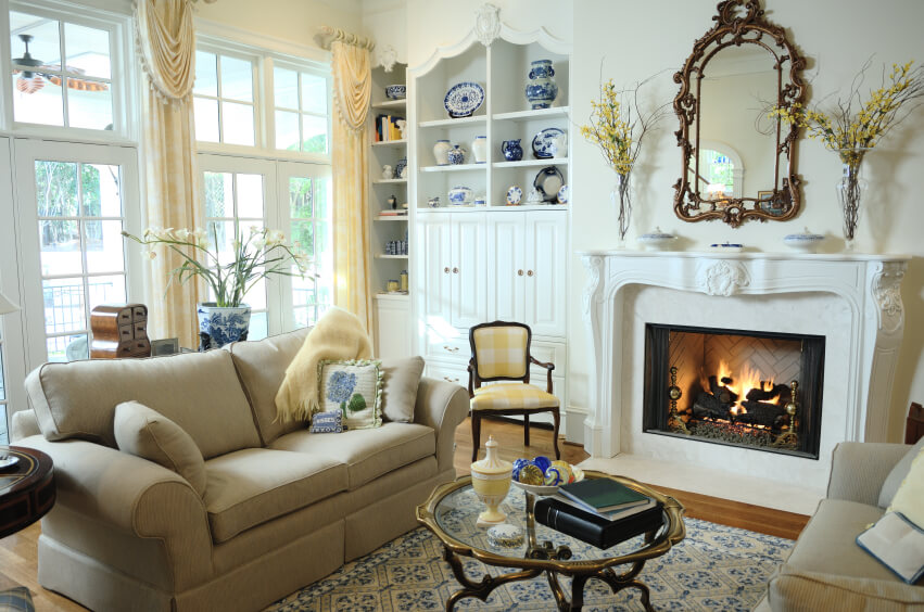 A small living room with an ornate fireplace mantle and a screened  wood-burning fireplace