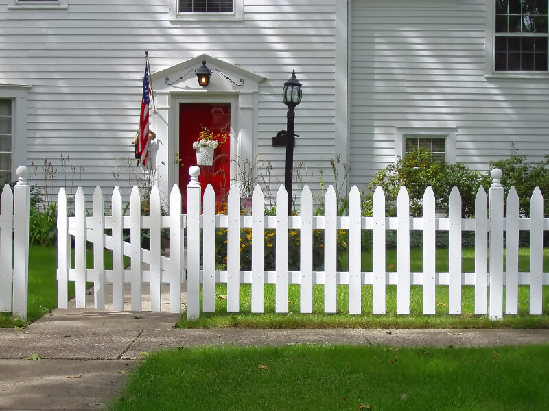 simple white picket fence in front of a gray house