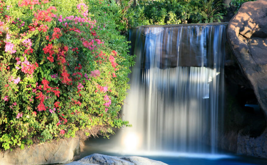 "A constantly cascading waterfall falling in a steady sheet on either side of an artificial stone ""bridge."" Flowering bushes grow in a thick mass above the pool."