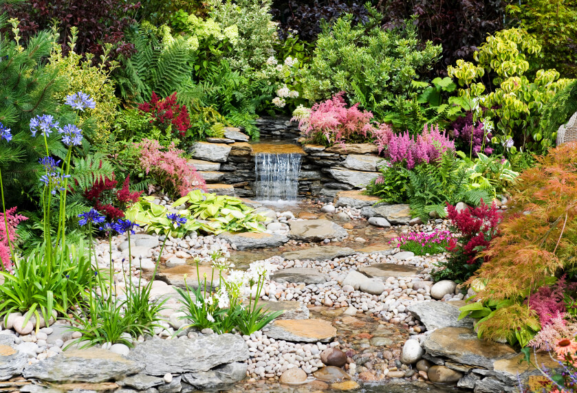 In a more expansive garden, a small waterfall leads out from between flowered bushes and splashes down into a shallow, winding stone stream ending in a larger pond.