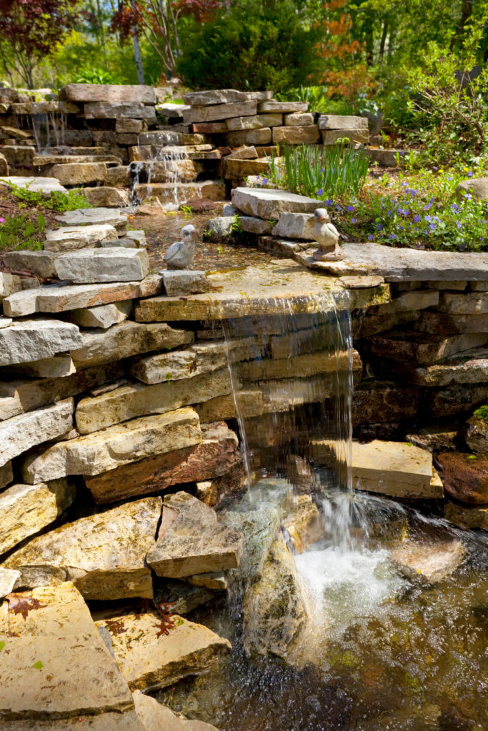 Layered sedimentary stones make up this water well and for Garden pond waterfall ideas