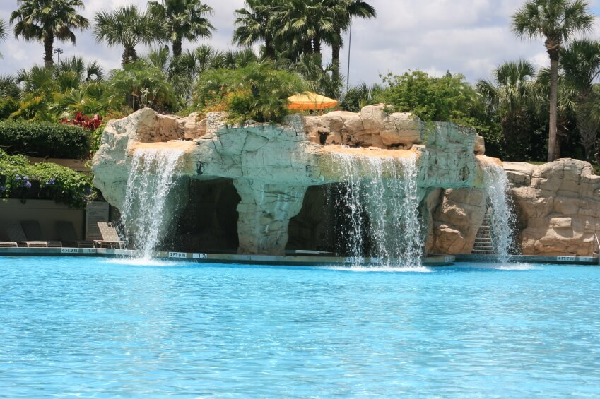 "A tropical resort pool with three waterfalls cascading down over three shadowed ""caverns"" in the artificial stone."