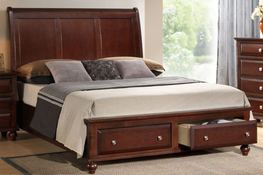 A platform bed with two drawers off of the footboard. The frame is a solid wood with a rich cherry finish. The headboard is a simple, classic piece with three panels.