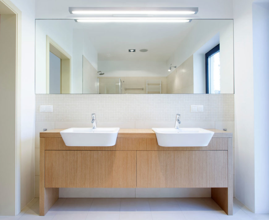 interesting modern basins hang over a natural wood vanity cabinet while a shared mirror hangs