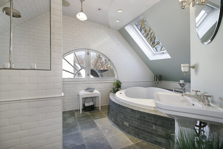 Luxury Bathroom Featuring Beautiful Natural Light From An Arched Window And Skylight