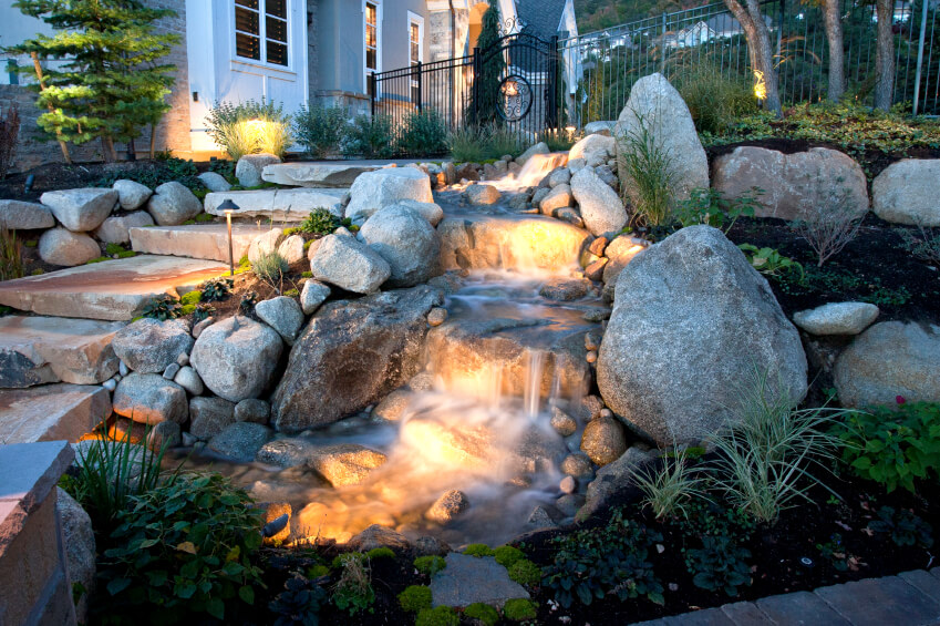the entrance to this gated backyard runs past a small waterfall and