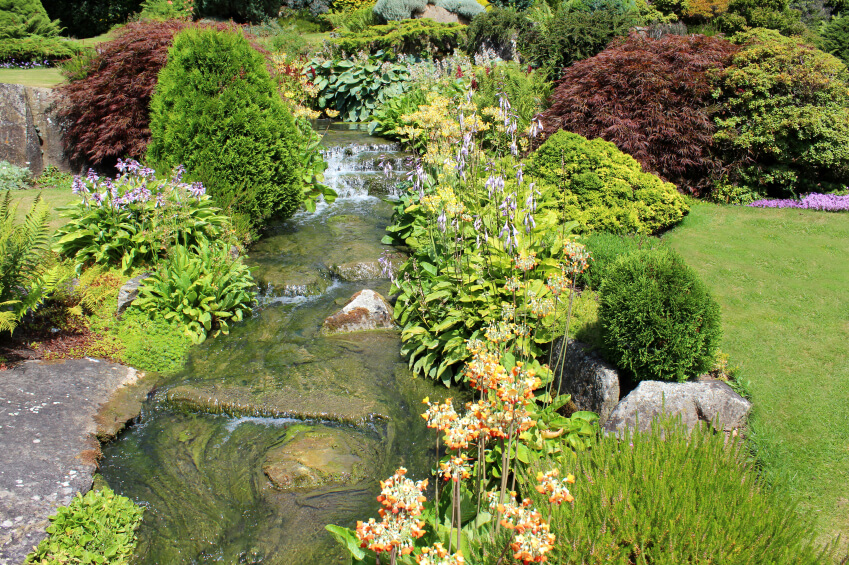 The erosion caused by the stream over time has worn fantastic swirls into the stone bed of this shallow stream, with a waterfall at the top. Beautiful flowers line the edges of the stream.