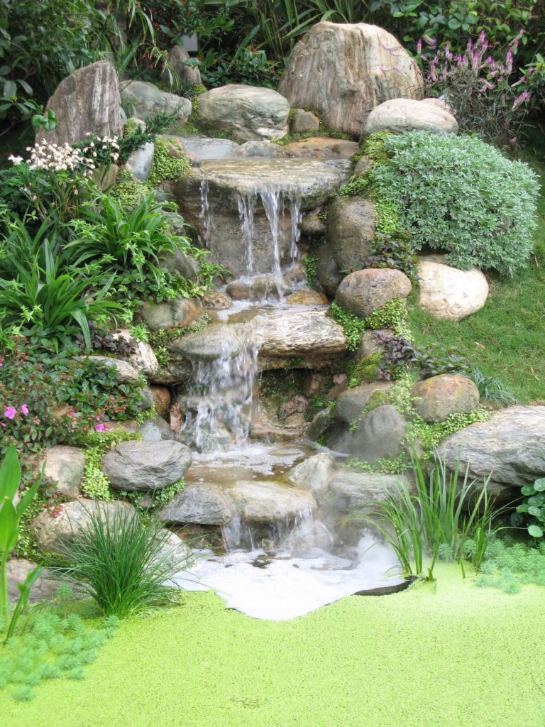 A three tiered stone waterfall that ends in a tiny but for Garden waterfall