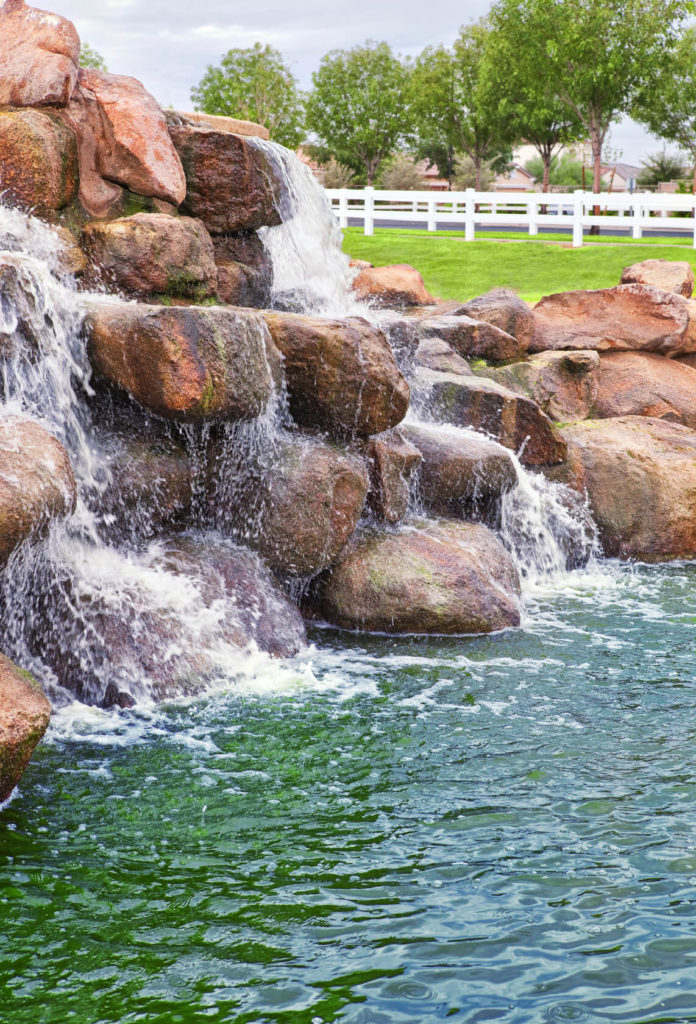 A waterfall constructed of large boulders. The water rushes down into the large naturally filtering swimming pool.