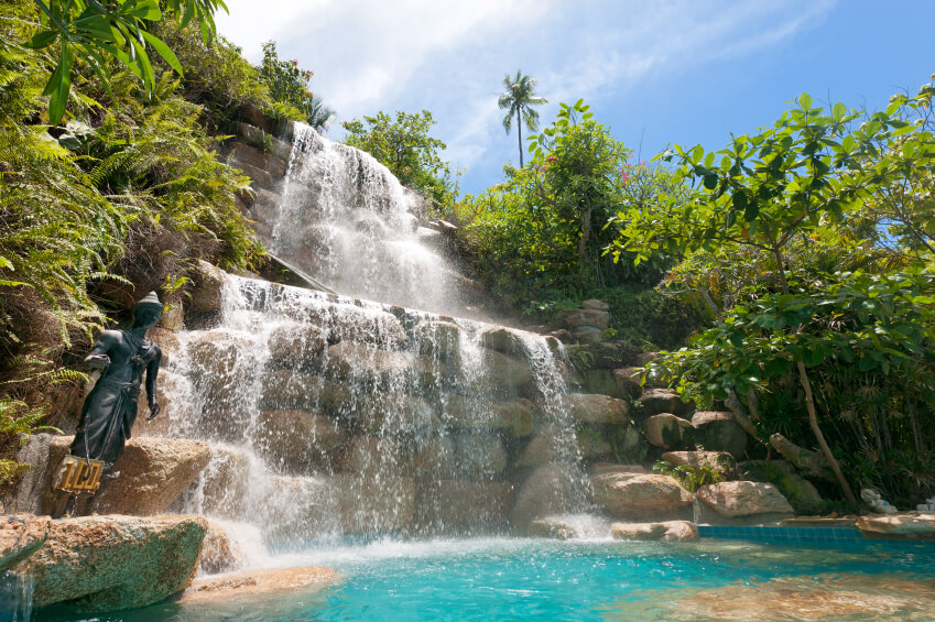 An enormous artificial waterfall located at a tropical resort. The sheer enormity of the structure creates a great atmosphere.