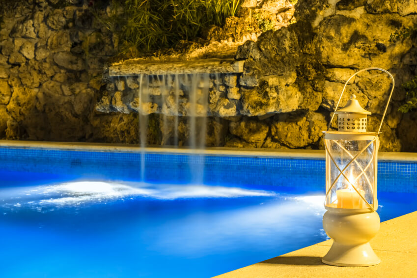 pool waterfall lighting. a lighted rock waterfall with smooth outcropping to gently cascade down into the pool lighting w