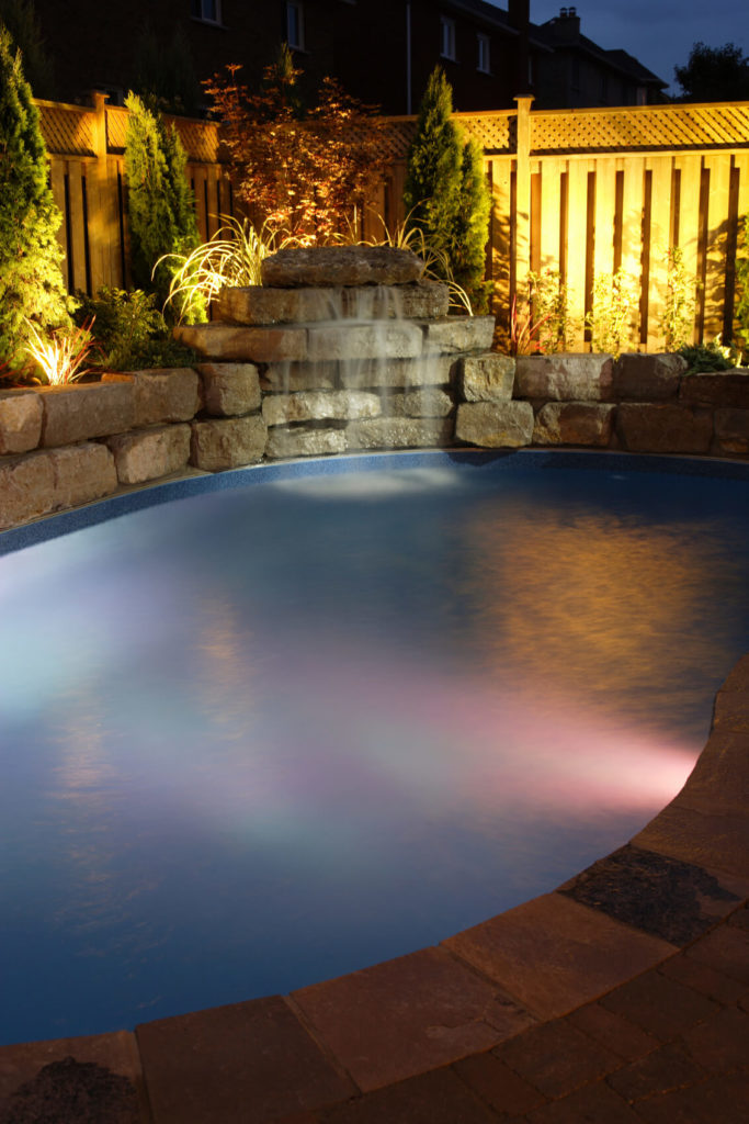 A simple stone waterfall feature for added ambiance to the pool lighting and the lighting in the landscaping behind the water feature.
