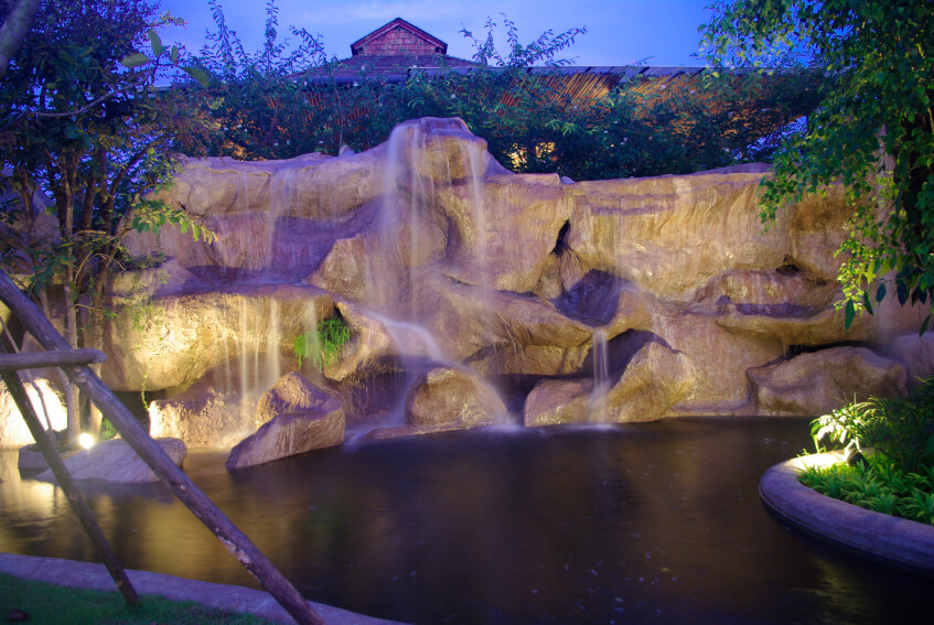 Another view of the above waterfall at night that pours majestically into the swimming pool.