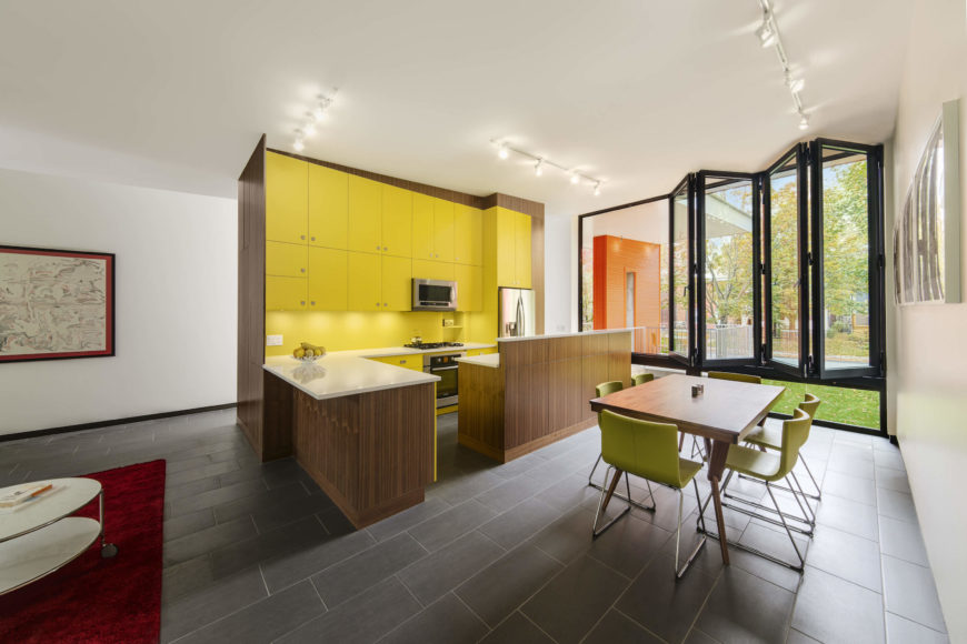 On the upper level, we see the open-plan kitchen area, highlighted by bright yellow cabinetry and rich wood tones throughout.