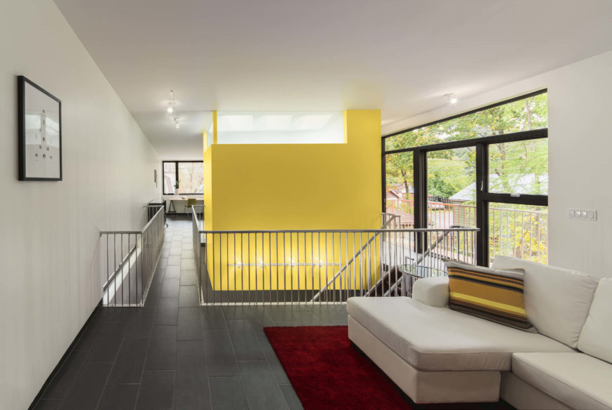 Moving toward the rear of the home, we see the bathroom, suspended in yellow, at center, and the wraparound patio at right.