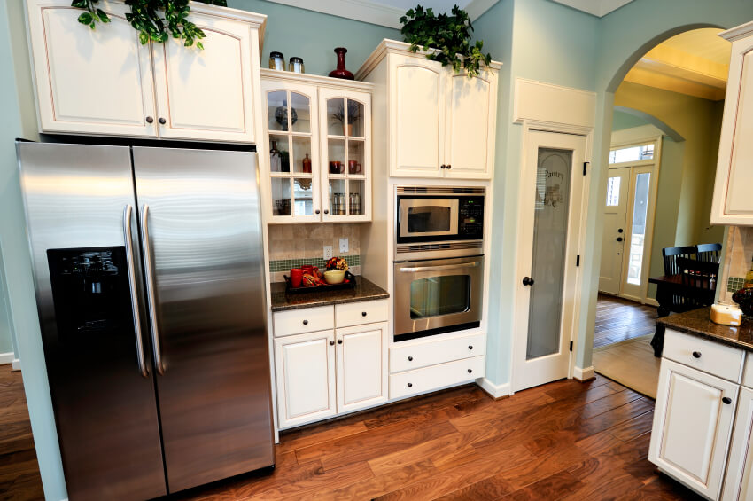 Soft sky blue walls ensconce this kitchen, sporting sharp white cabinetry and rich hardwood flooring. Stainless steel appliances add to the bold contrast.