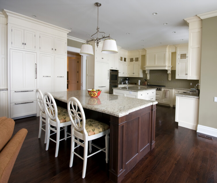 Across this wide expanse of dark wood kitchen flooring, we see two large islands: a cooktop with built-in sink and a larger space for in-kitchen dining. White cabinets with steel hardware surround the large space.