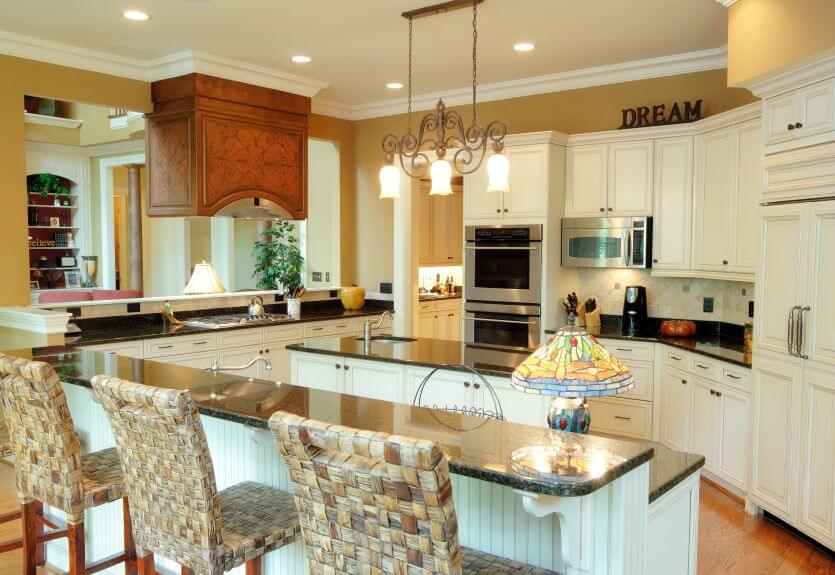 A Kitchen With Ample Countertop Space That Includes An Island And An Eat In Bar