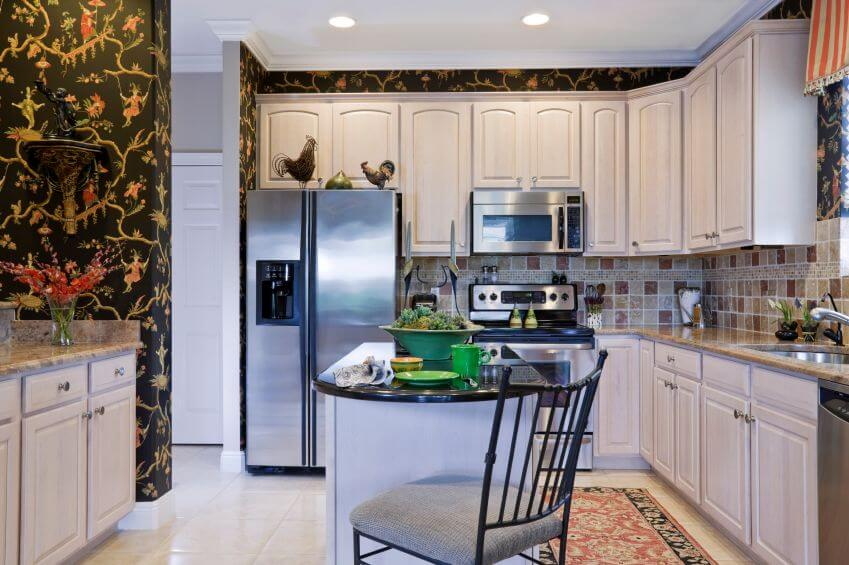 An eclectic kitchen with a small island and an ornate black wallpaper that  creates an interesting
