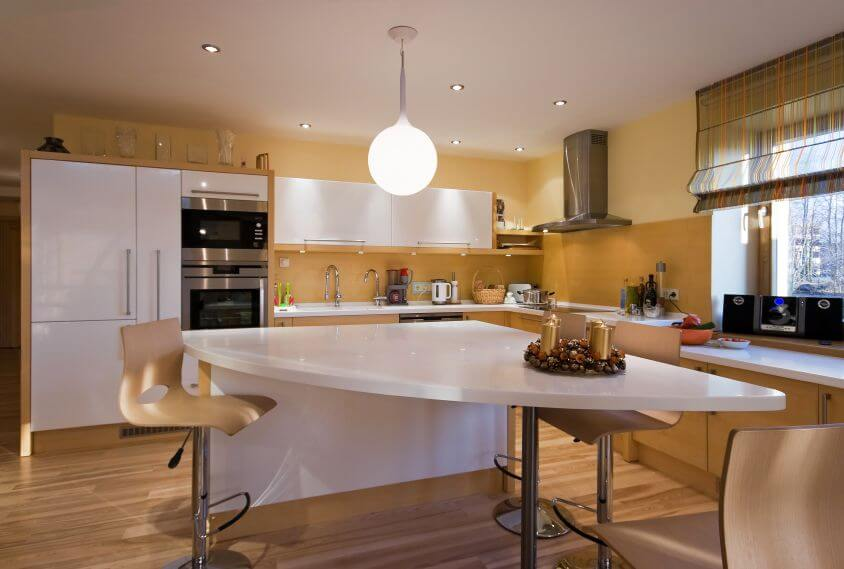 A Contemporary And Modern Kitchen With A Spacious Island In Sleek White That Matches The Minimalist