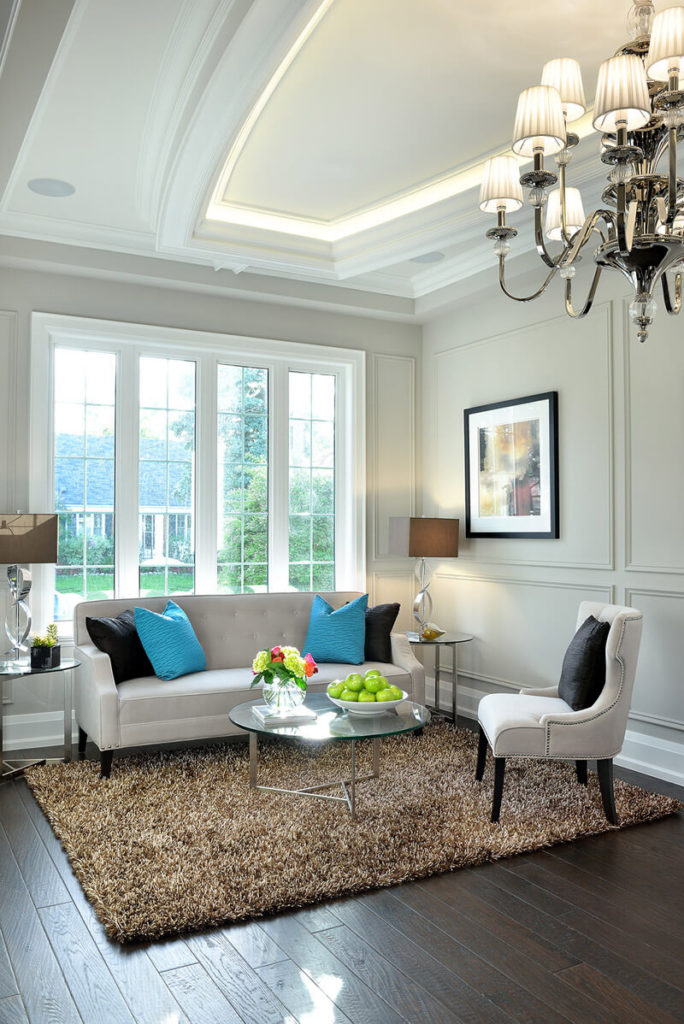 A Small Living Room In White And Beige With A Splash Of Blue And Black.