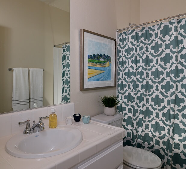 This bathroom rephrases the blue tones of the master bedroom on the patterned shower curtain, beside a traditional white toned setup.