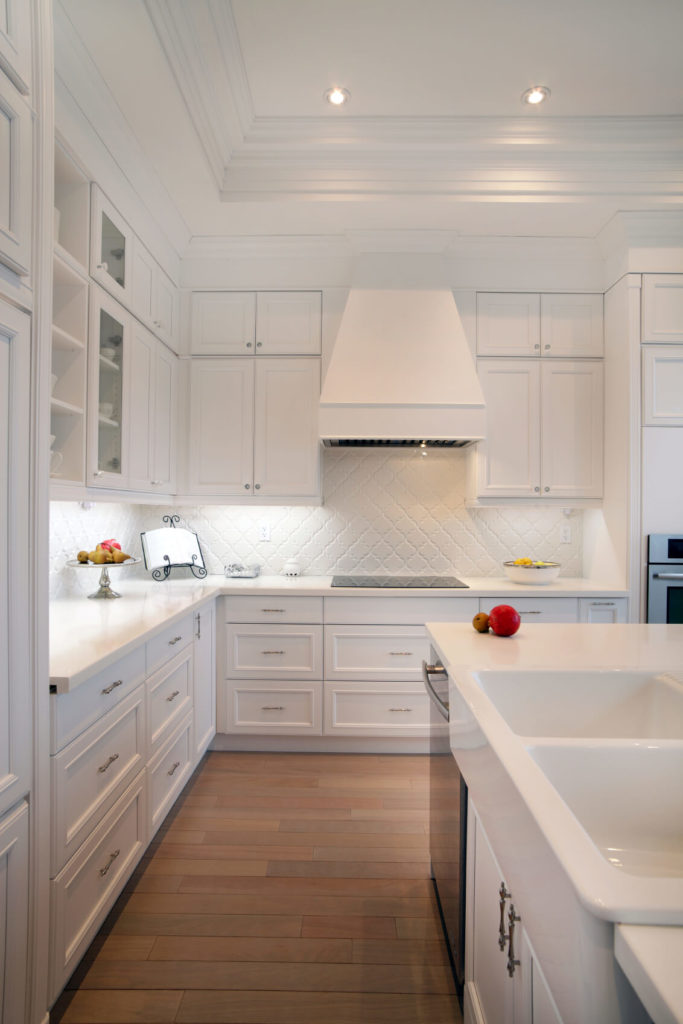 The island in this white kitchen houses a large basin sink, freeing the surrounding countertops up for workspace. An intricately patterned white backsplash helps lighten the look.