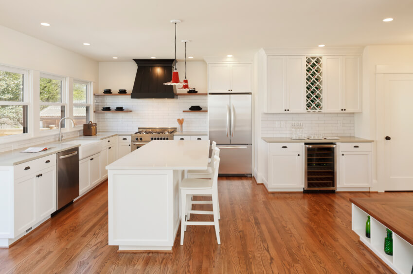 This open design kitchen centers on a lengthy white island with sleek white marble countertop. Matching bright cabinetry with dark hardware surrounds the large space, anchored upon rich hardwood flooring.
