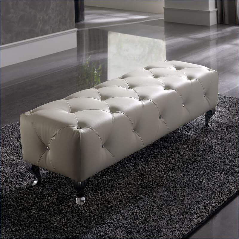 A Low Tufted Ottoman With Crystal Ons And Elegant Curved Legs Perfect As An