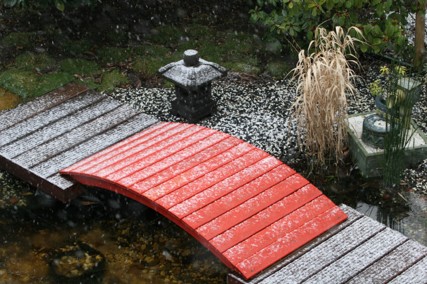 a small red footbridge without railings is caught in a sudden snowstorm soft white flakes