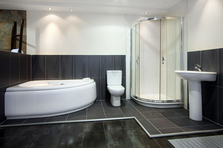 Floor Tiling And A Raised Black Tile Surface Surrounding The Bath