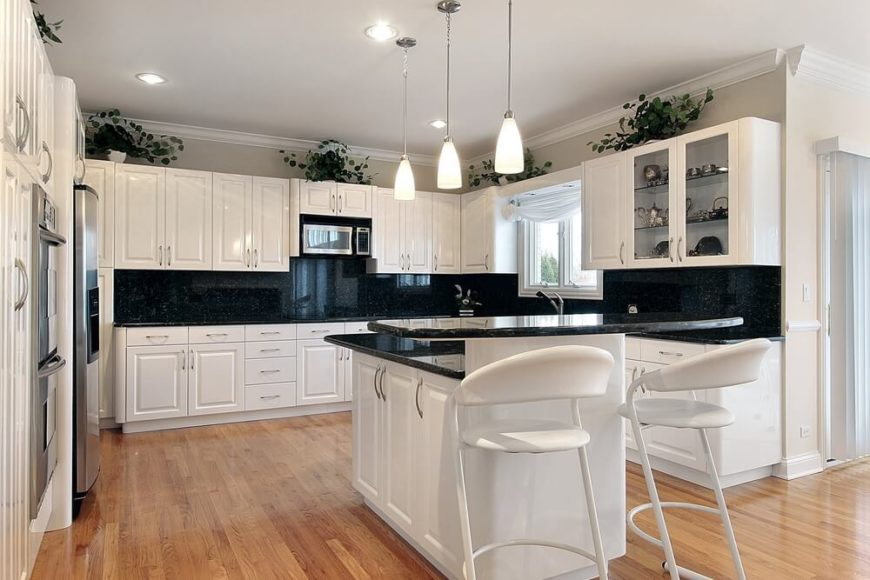 This contemporary kitchen boasts a high contrast look, courtesy of white cabinetry and jet black countertops and backsplash. Warm toned hardwood floors add an earthy element to the brightly lit space.