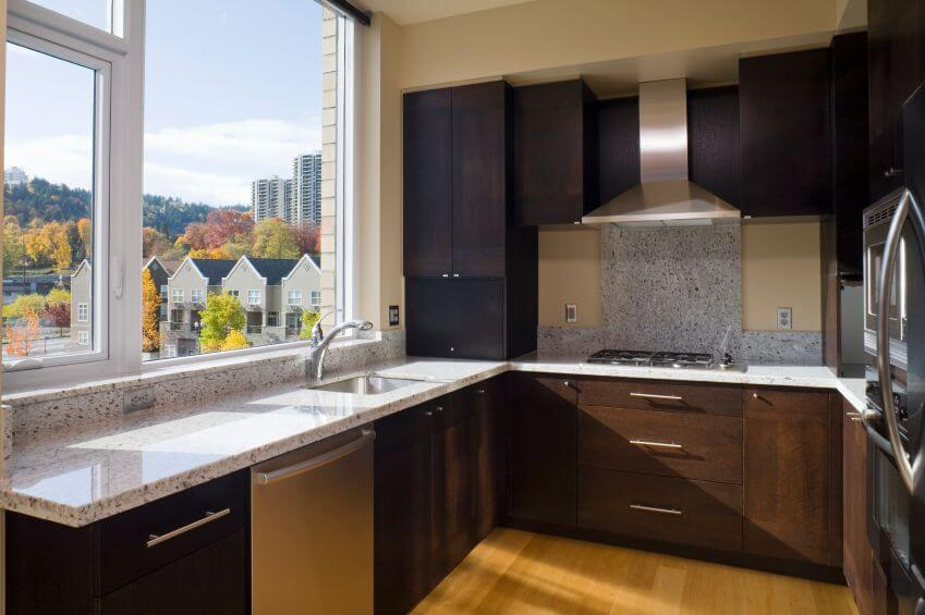 A Modestly Sized Apartment Kitchen In Dark Wood And Light Granite With  Beige Walls. Large Part 96