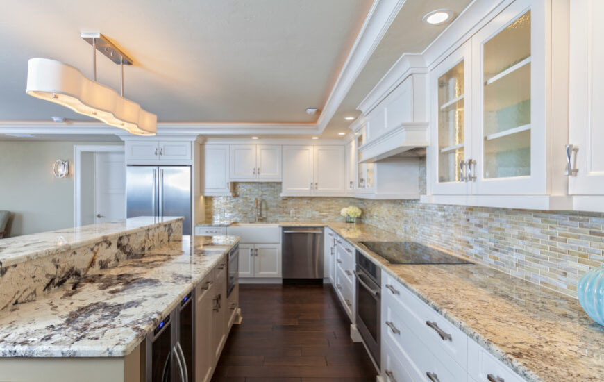 Rich granite countertops cover the bold white drawers in this kitchen, with thin tile bricks sandwiched below the upper cabinetry. The two-tier island houses a appliances, storage, and plenty of dining space.