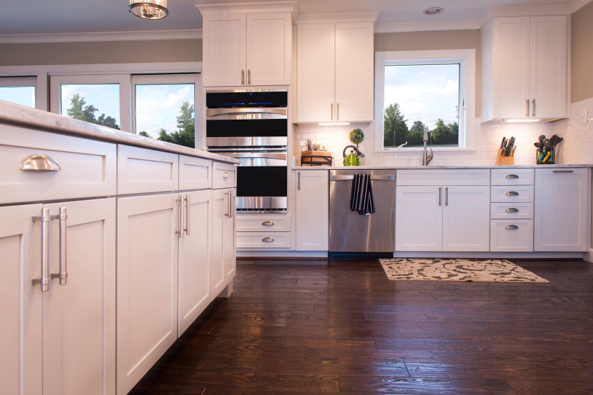 Sleek White Cabinetry With Stainless Steel Hardware Glows In This Open Plan  Kitchen, Over Rustic