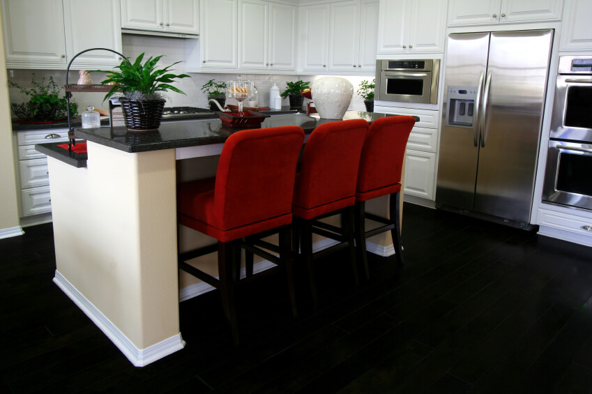 This ultra-contrasting kitchen sets white cabinetry over a deep black floor, with matching black countertops. A trio of red upholstered bar stools stand at the two-tier island, offering a burst of color.