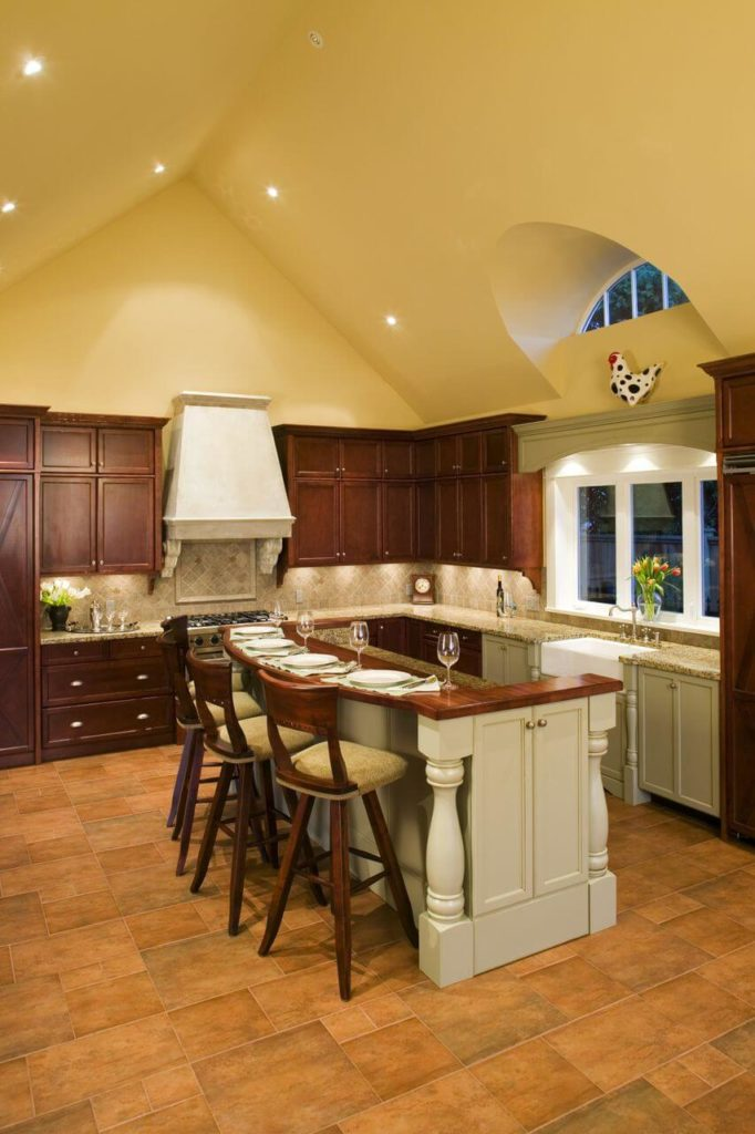 An L Shaped Kitchen With A Large Center Eat In Island In White And