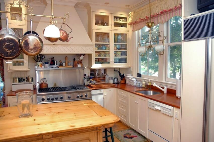 A Country Style Kitchen With An Overhanging Pot Rack And Glass Faced Cabinets On Either