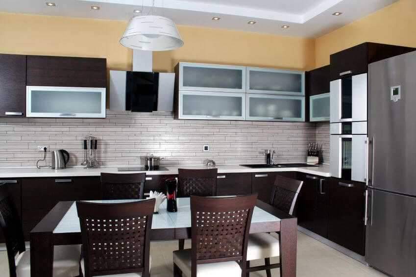 A Modern L Shaped Kitchen With A Light Gray Tile Backsplash And A Dining Table
