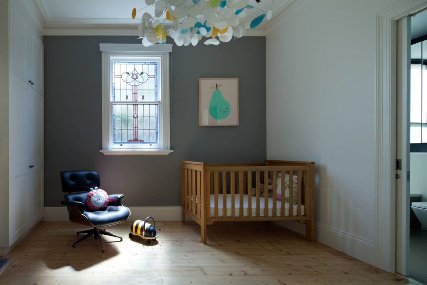 Another Eames chair graces this baby room, which isn't over saturated with a typical color for a nursery room. Compared to the kitchen, the storage space has a more classic set up, with drawer pulls included and paneled cabinet fronts.