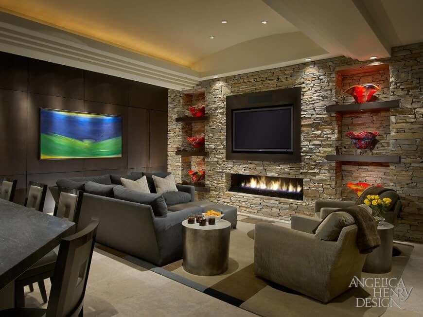 living room has an entire stone wall with a gas burning fireplace