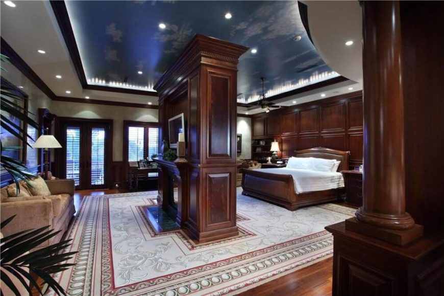 an absolutely stunning master bedroom in polished hardwood a center fireplace is dual sided