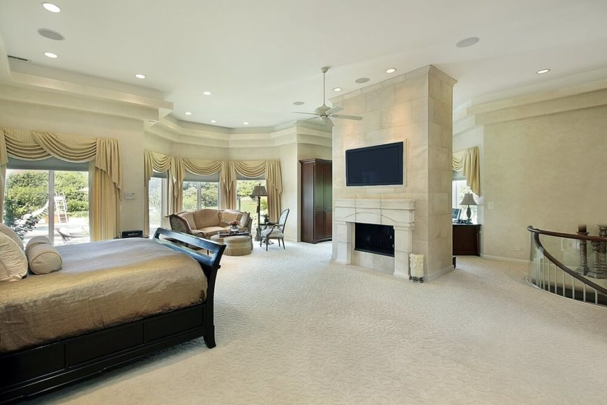 spacious master bedroom with a spiral staircase leading down to a