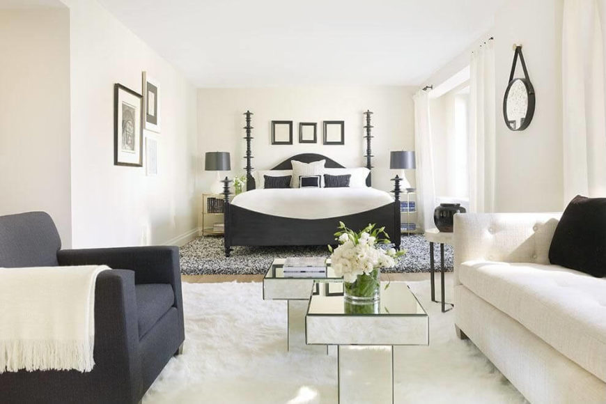 a bright white bedroom with charcoal gray accents and a plush rug beneath the bed - Bedroom Sofa Ideas