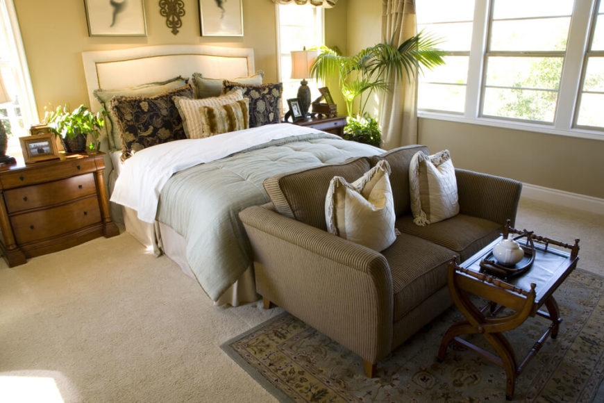 At The Foot Of The Bed Is A Low Profile Corduroy Loveseat With A Small