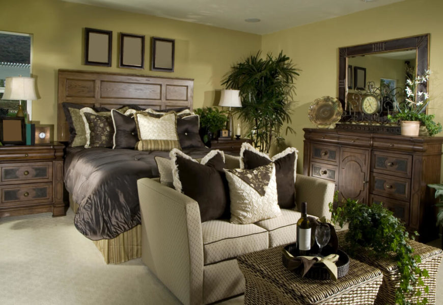 A Smaller Master Bedroom With A Beige Loveseat At The Foot Of The Bed. A