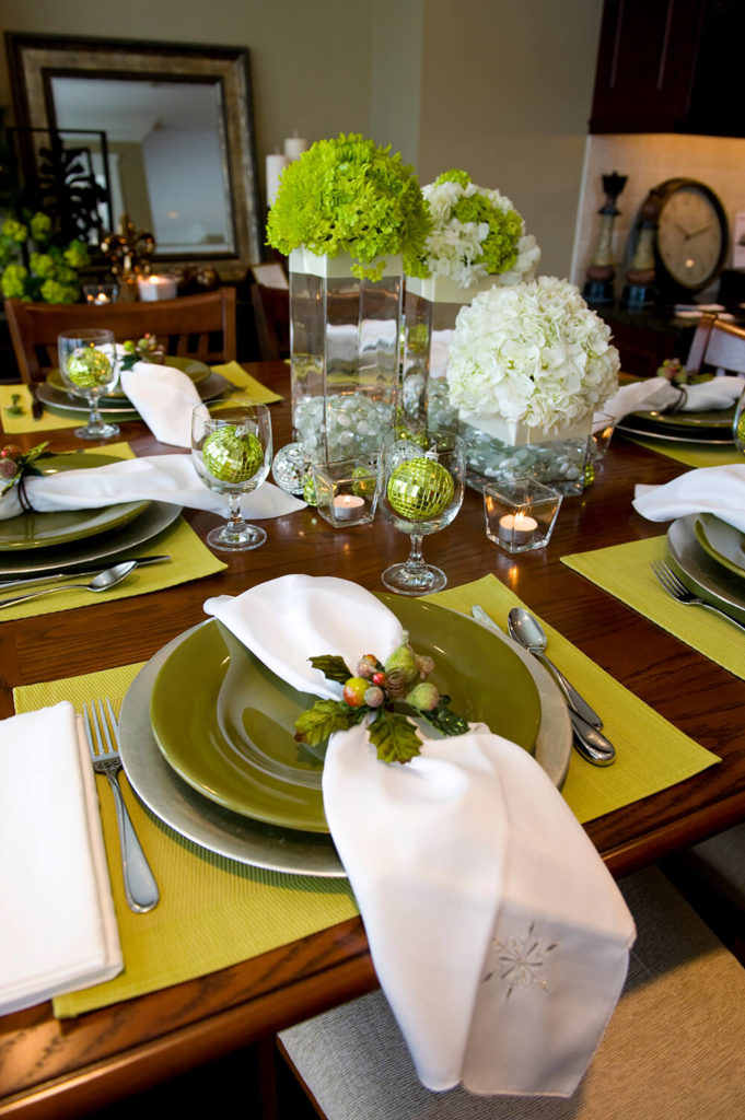 A Festive Holiday Place Setting On A Light Green Placemat. The White Napkin  Has An