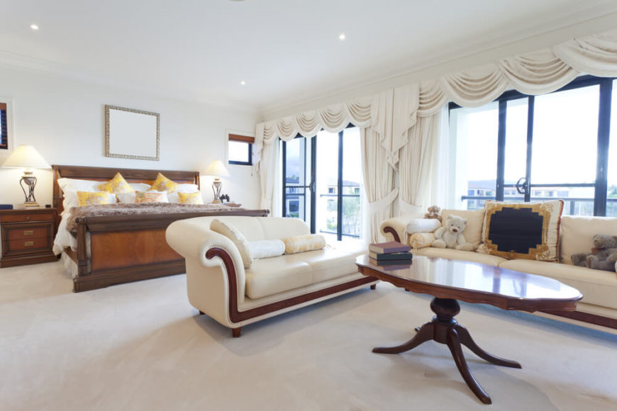 A light and bright master bedroom with a large sofa and chaise lounge in  cream with
